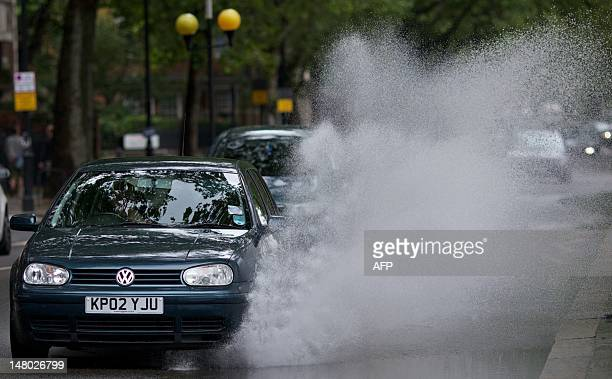 A car drives through a large puddle left after heavy rain in central London England on July 8 2012 AFP PHOTO/ANDREW COWIE