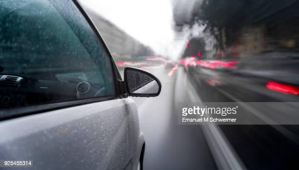 car drives through a rainy city