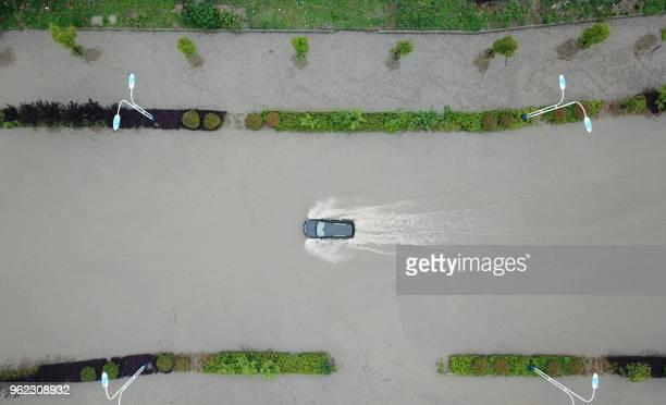 TOPSHOT A car drives through a waterlogged street after heavy rainfall in Yangzhou in China's eastern Jiangsu province on May 25 2018 Heavy rain...