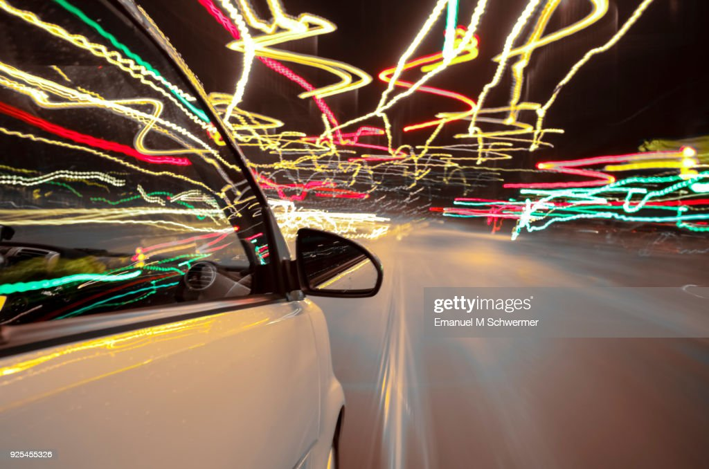 car drives through Berlin while night - right side of the car with wing-mirror in foreground - long exposure : Stock Photo