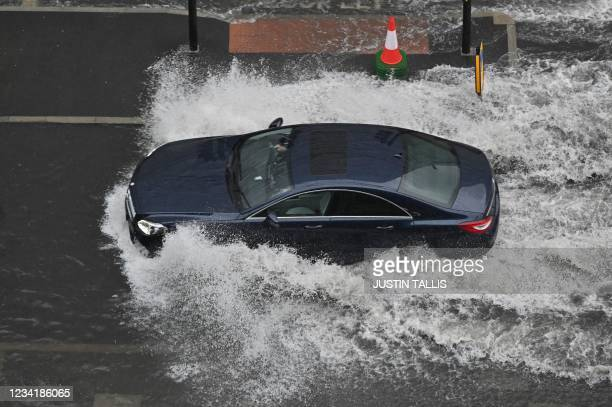Car drives through deep water on a flooded road in The Nine Elms district of London on July 25, 2021 during heavy rain. - Buses and cars were left...