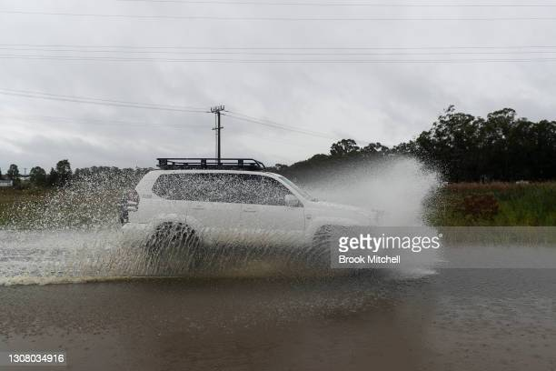 Car drives through flood waters on March 20, 2021 in Pitt Town, Australia. Heavy rain and flooding has trigger evacuations on the New South Wales mid...