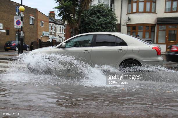 Car drives through flooding on a road in East London following flash flooding today afternoon. Extreme heat in the previous week has given way to...