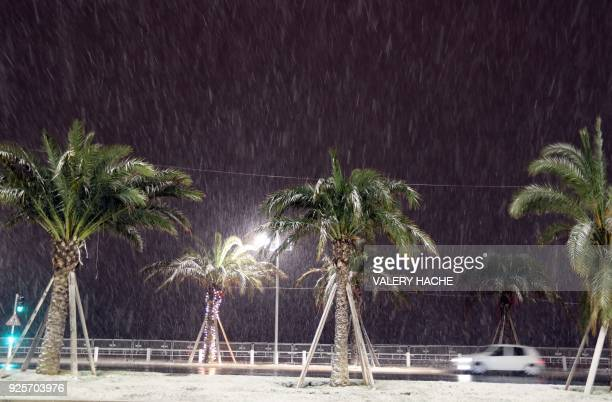 A car drives through heavy snowfall along the Promenade des Anglais on February 28 2018 in Nice HACHE