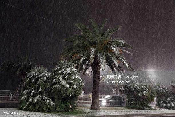 A car drives through heavy snowfall along the Promenade des Anglais on February 28 2018 in Nice / AFP PHOTO / VALERY HACHE