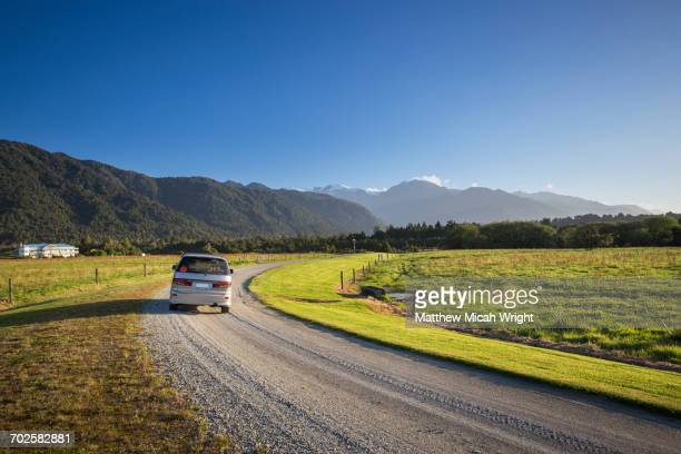 A car drives through New Zealand countryside.