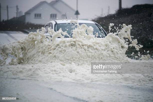 A car drives through sea foam whipped up by the wind of Hurricane Ophelia at Trearddur Bay on October 16 2017 in Holyhead Wales Hurricane Ophelia...