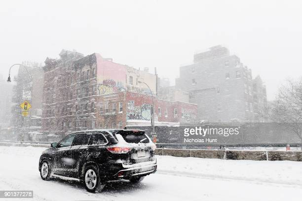 Car drives through snow covered streets during a massive winter storm on January 4 2018 in New York City As a major winter storm moves up the...