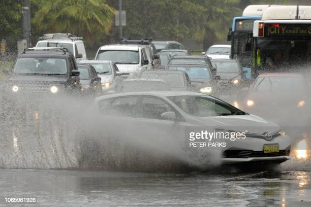 A car drives through water caused by heavy rain on a road in Sydney on November 28 2018 Flights were cancelled railway lines closed and motorists...