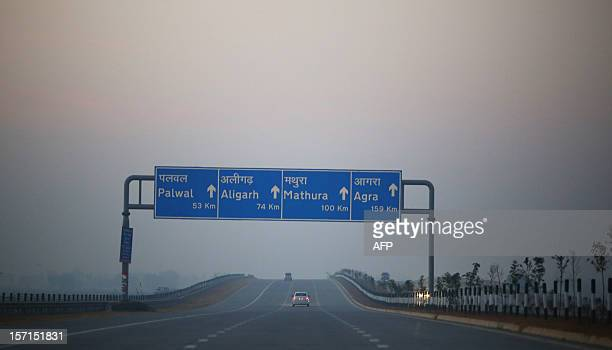 A car drives under a sign on a recently opened Indian highway connecting New Delhi to Agra in Uttar Pradesh state on November 28 2012 A highway that...