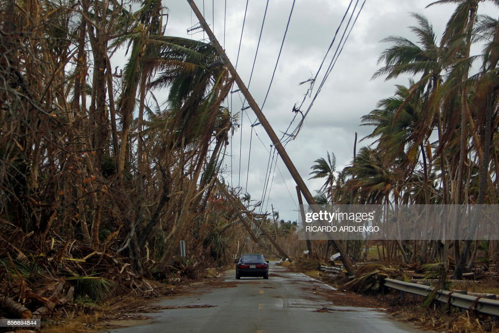 A car drives under tilted power line poles in the aftermath of Hurricane Maria in Humacao, Puerto Rico on October 2, 2017. President Donald Trump strenuously defended US efforts to bring relief to storm-battered Puerto Rico, even as one island official said Trump was trying to gloss over 'things that are not going well,' two weeks after devastating Hurricane Maria left much of the island without electricity, fresh water or sufficient food. / AFP PHOTO / Ricardo ARDUENGO