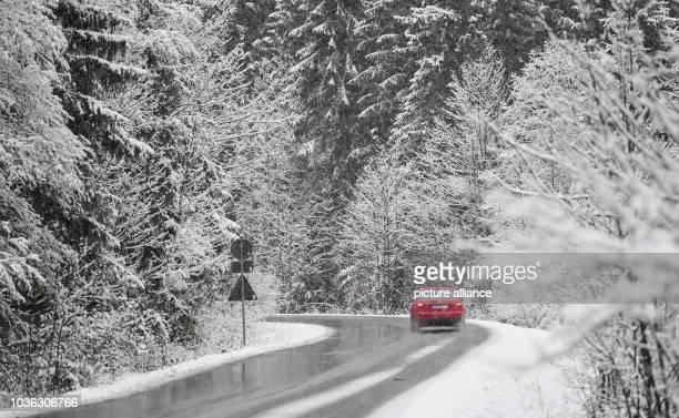 Car driving along a snowy street near Kruen, Germany, 6 November 2016. PHOTO: SVEN HOPPE/dpa | usage worldwide