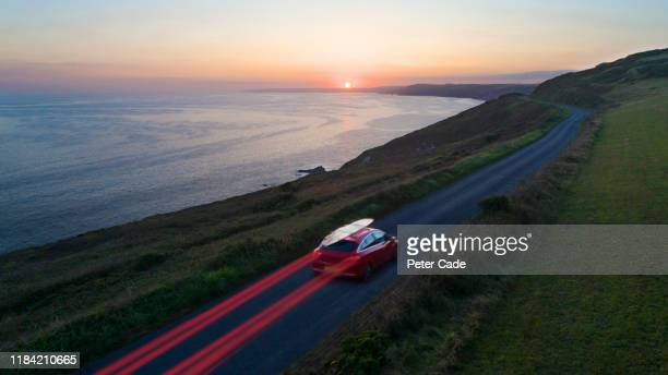 car driving along coastal road at sunset - road trip stock pictures, royalty-free photos & images