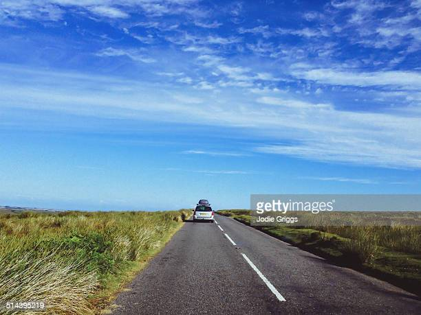 car driving along straight stretch of road - exmoor national park stock pictures, royalty-free photos & images