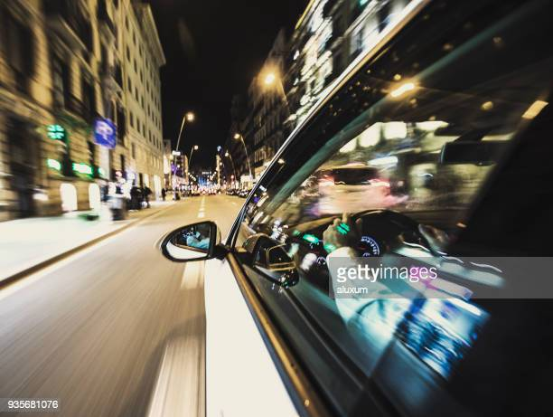car driving at night in the city - side view mirror stock photos and pictures