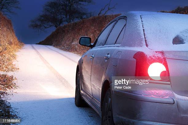 car driving down country lane in the snow