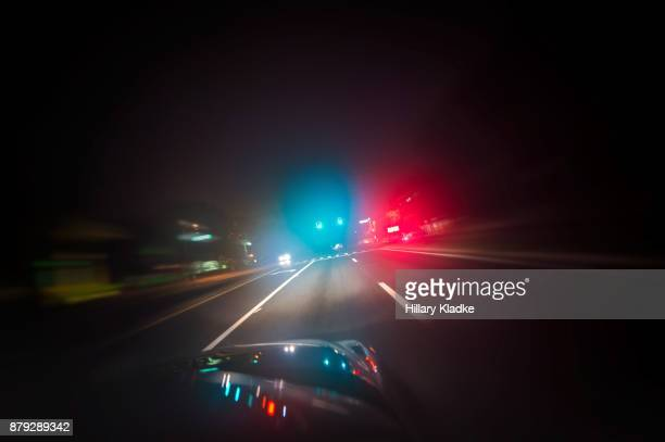 car driving down road with red and blue lights - forze di polizia foto e immagini stock