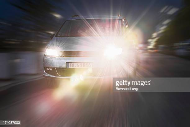 Car driving down street, headlights on
