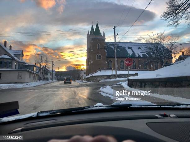 car driving down street in rumford, maine near church during winter - maine stock pictures, royalty-free photos & images