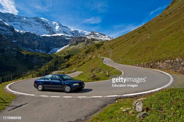 Car driving in a hairpin bend on the mountain road to the pass Klausenpass against the peaks of the Glarus Alps near Urnerboden, Canton of Uri,...