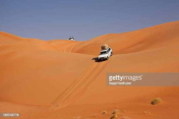 Car driving in the desert between sand dunes