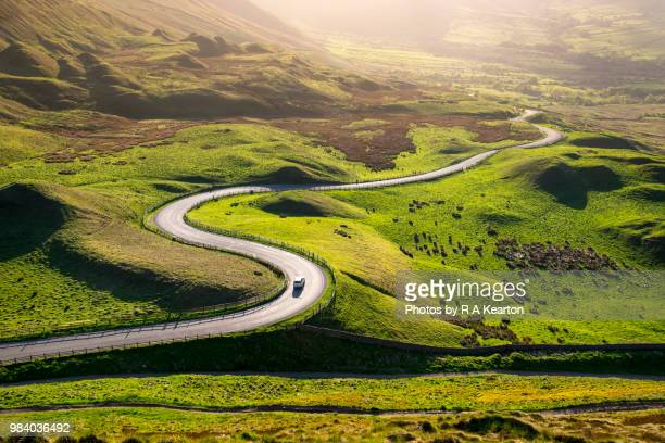 car driving in the hills of england on a sunny evening - groot brittannië stockfoto's en -beelden
