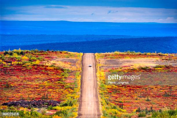 Car driving in the wilderness through the colorful Tundra on the Dempster highway in Autumn - Yukon, Canada