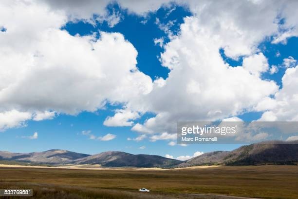 Car driving near mountains in remote landscape