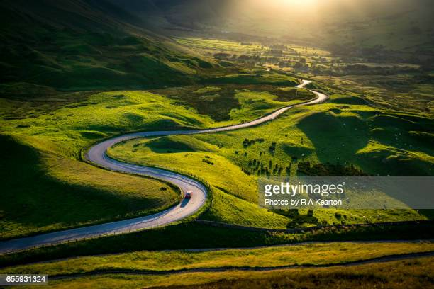 car driving on a bendy road in glorious sunlight - paisaje espectacular fotografías e imágenes de stock
