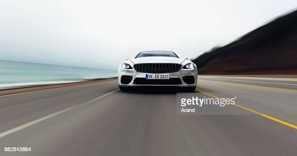 car driving on a road by sea - front view stock pictures, royalty-free photos & images