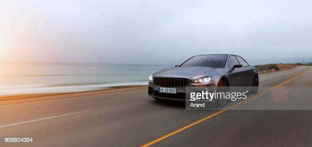 car driving on a road by sea - cars stock photos and pictures