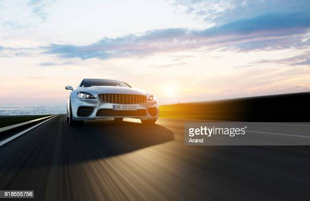 car driving on a road by sea - road stock pictures, royalty-free photos & images