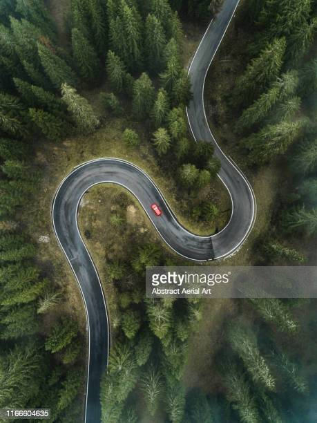 a car driving on a winding forest road seen from directly above, dolomites, italy - winding road stock pictures, royalty-free photos & images