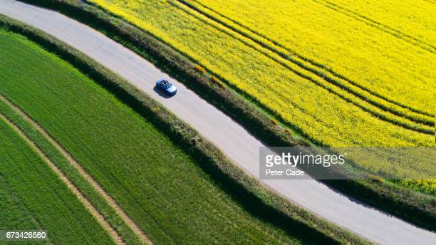 car driving on country road between fields - country road stock pictures, royalty-free photos & images