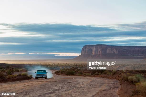 Car driving on dirt road in desert, Monument Valley, Utah, United States