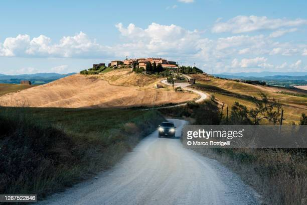 car driving on gravel road in tuscany, italy - val d'orcia stock pictures, royalty-free photos & images