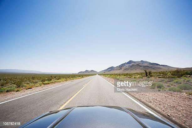 Car driving on highway through the desert