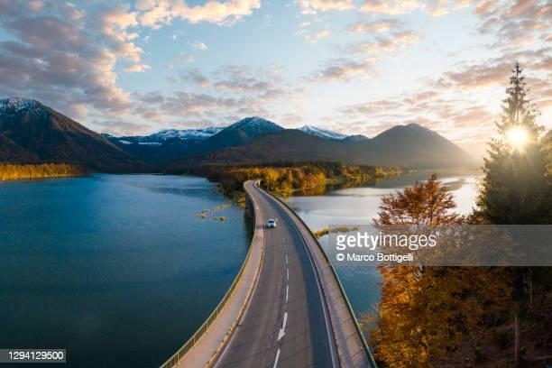 car driving on idyllic bridge over sylvenstein lake, germany - germany stockfoto's en -beelden
