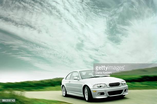 car driving on road with clouds - landfahrzeug stock-fotos und bilder