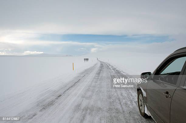 Car driving on rural road in snowy landscape