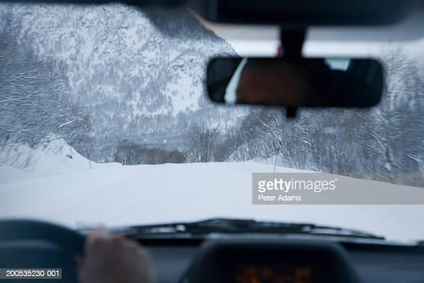 Car driving on snow covered mountain road, view from car