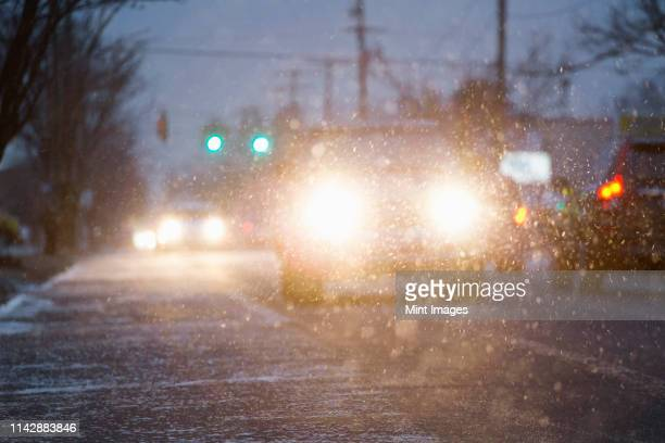 car driving on snowy urban street at night - winter weather stock photos and pictures