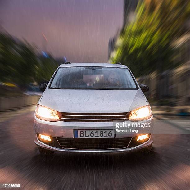 car driving on urban street in the rain - frontaal stockfoto's en -beelden