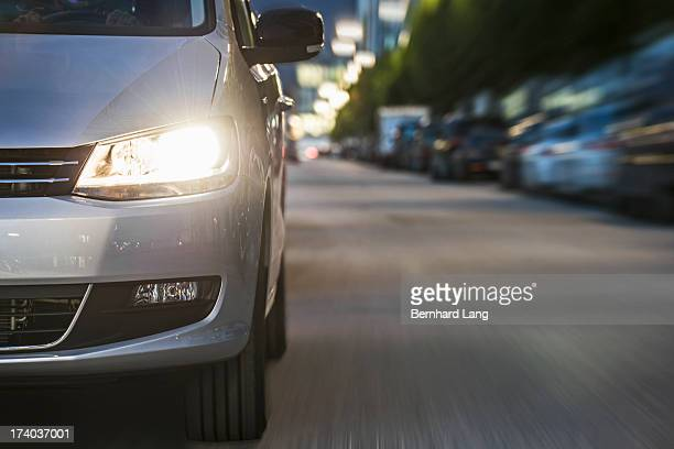 car driving on urban street, low angle view - headlight stock pictures, royalty-free photos & images
