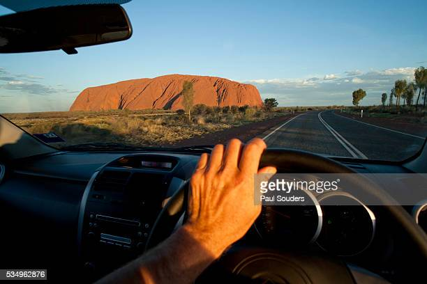Car Driving Toward Ayers Rock in the Australian Outback