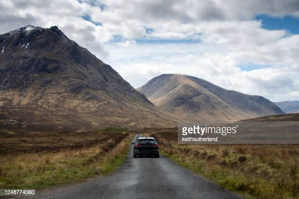 car driving towards mountains, glencoe, scottish highlands, scotland, uk - rear view stock pictures, royalty-free photos & images
