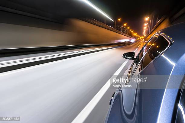 car drivving fast in the tunnel - dividing line road marking stock photos and pictures