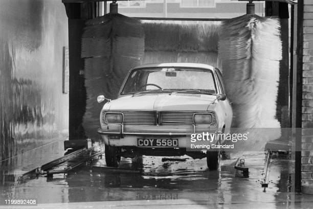 A car emerges from the wraps in a car wash at an Alan Pond Garage in England August 1976