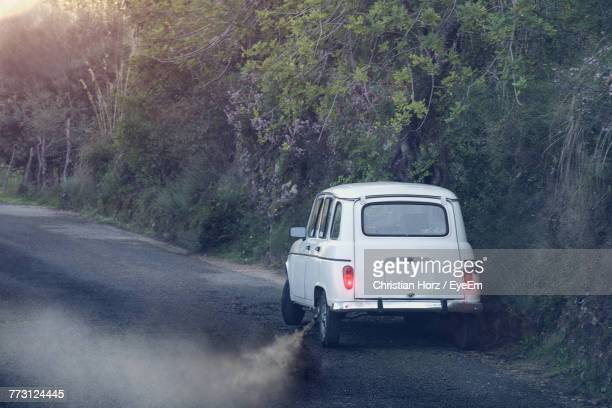 car emitting smoke on road - pollution photos et images de collection
