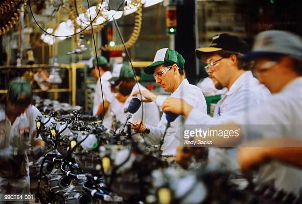 car engine assembly, workers adjusting engine block valve - fließbandfertigung stock-fotos und bilder